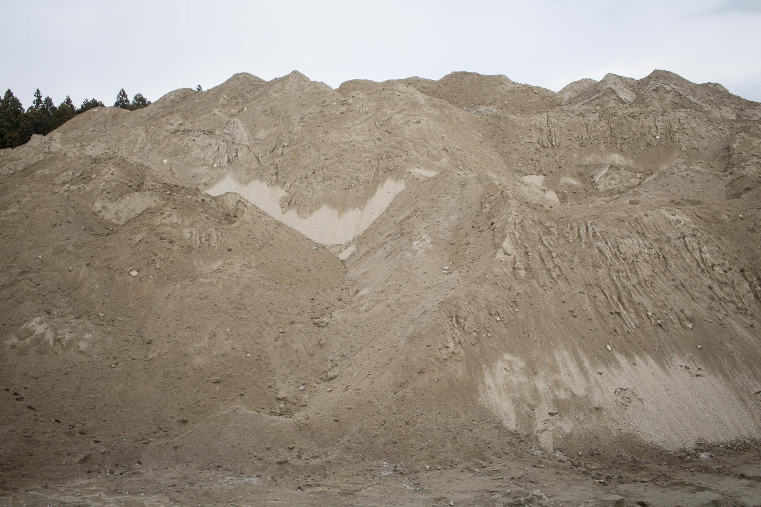 Heaps of sand kept to be transported to replace the soil in contaminated fields. Sandoil is brought by mining the mountains from regions which are not contaminated